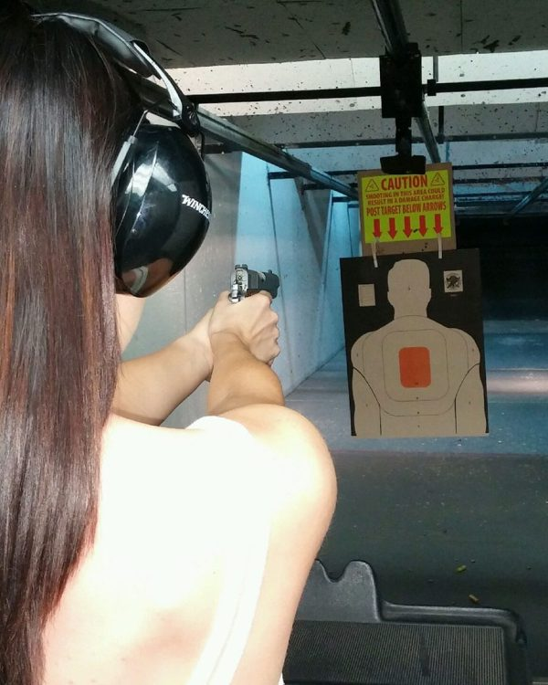 Woman shooting at a target using her 9mm package